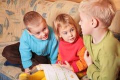 Kinder lasen Buch auf Sofa stockfotografie