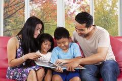 Kinder lasen ein Geschichtenbuch mit Eltern Lizenzfreies Stockfoto