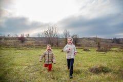 Kinder laufen gelassen in das Feld Kinderspiel auf dem Gebiet an der goldenen Stunde stockbilder