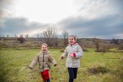 Kinder laufen gelassen in das Feld Kinderspiel auf dem Gebiet an der goldenen Stunde stockfotografie