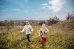 Kinder laufen gelassen in das Feld Kinderspiel auf dem Gebiet an der goldenen Stunde lizenzfreie stockfotos