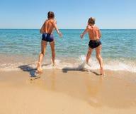 Kinder laufen gelassen zum Meer Stockbild