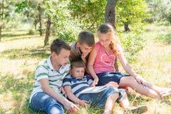 Kinder lernen in der Natur, vier Kinder lasen ein Buch im Park im Freien Schüler bereiten sich für Schule vor stockbild