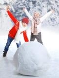 Kinder machen einen Schneemann in der Winterzeit Stockbilder