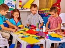Kinder machen etwas aus farbigem Papier heraus Stockfotos