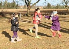 Kinder - Mädchen, die das Büffelleder des Blinders spielen Stockfotos