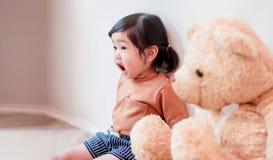 Kinder mit überraschendem Gesicht ein zwei Jahr-altes Mädchen, das nahe gelegenes Th stationiert Stockfotografie