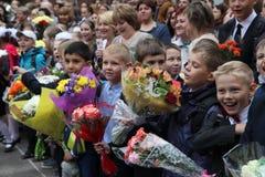 Kinder mit Blumen gehen Schule zur September erster Stockfotos