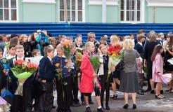 Kinder mit Blumen nahe der Schule Lizenzfreie Stockbilder
