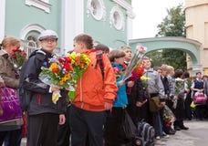 Kinder mit Blumen nahe der Schule Stockfotografie