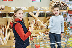 Kinder mit Brot im Supermarkt Stockfotos