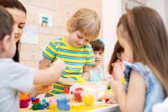 Kinder mit buntem Lehmspielzeug des Lehrerspiels im Kindertagesstätte stockfotografie