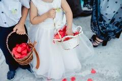 Kinder mit dem Korb, der rosafarbene Blumenblätter wirft lizenzfreie stockfotografie