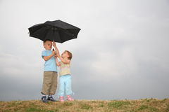 Kinder mit dem Regenschirm Stockbild