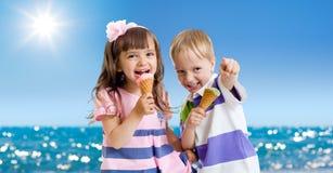 Kinder mit der Eiscreme im Freien. Küste am Sommer Lizenzfreie Stockfotografie