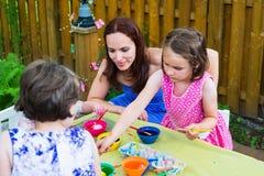 Kinder mit der Mutter, die draußen Ostereier färbt Stockfotos
