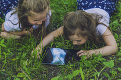 Kinder mit der Tablette, die im Gras liegt Lizenzfreie Stockfotografie