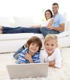 Kinder mit einem Laptop und Muttergesellschaftn Stockfotos