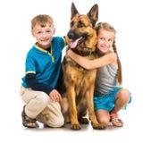 Kinder mit einem Schäferhund Stockfotos