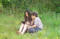 Kinder mit einer Tablette Stockfotos