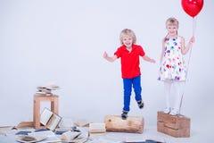 Kinder mit farbigen Ballonen Dem Foto wurde ein weißes Studio eingelassen Los Bücher liegen auf dem Boden Stockfoto