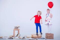 Kinder mit farbigen Ballonen Dem Foto wurde ein weißes Studio eingelassen Los Bücher liegen auf dem Boden Lizenzfreies Stockfoto
