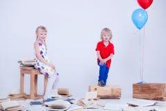 Kinder mit farbigen Ballonen Dem Foto wurde ein weißes Studio eingelassen Los Bücher liegen auf dem Boden Lizenzfreies Stockbild