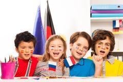 Kinder mit Flaggen auf Backen singend am Klassenzimmer Lizenzfreies Stockbild