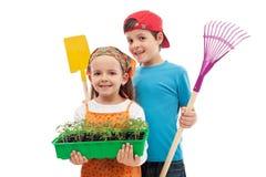 Kinder mit Frühlingssämlingen und Gartenarbeithilfsmitteln Stockfotos