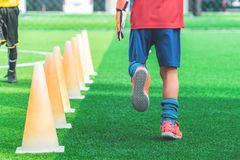 Kinder mit Fußballstiefeln ausbildend auf Ausbildungskegel auf Fußballboden stockfoto