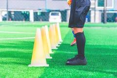 Kinder mit Fußballstiefeln ausbildend auf Ausbildungskegel auf Fußballboden lizenzfreie stockbilder