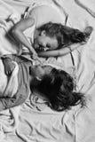 Kinder mit glücklicher Gesichtslüge im Bett lizenzfreies stockbild