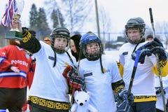 Kinder mit Hockeyschlägern und einem Cup Siegern in den Händen lizenzfreies stockfoto
