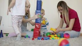 Kinder mit ihrer Mutter einen großen Turm von farbigen Würfeln errichten stock footage