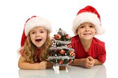 Kinder mit kleinem verziertem Baum zur Weihnachtszeit Stockbild