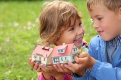Kinder mit kleinen Häusern des Spielzeugs in den Händen Lizenzfreie Stockfotos