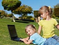 Kinder mit Laptop auf grünem Gras. Lizenzfreie Stockfotos