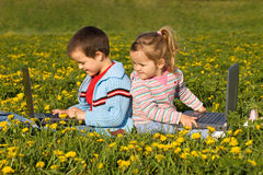 Kinder mit Laptopen auf dem Blumenfeld stockfotografie