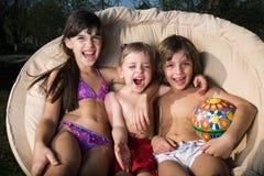 Kinder mit Lächeln in einem Lehnsessel Stockbild