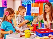 Kinder mit Lehrer im Vorschulkindergarten Stockbild
