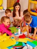Kinder mit Lehrer machen etwas aus farbigem Papier heraus lizenzfreie stockfotos