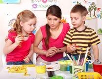 Kinder mit Lehreranstrich im Spielraum. Stockfotografie