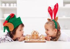 Kinder mit lustigen Weihnachtshüten und Lebkuchenhaus Lizenzfreie Stockfotografie