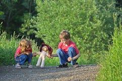 Kinder mit Puppe auf Pfad im Park lizenzfreies stockfoto