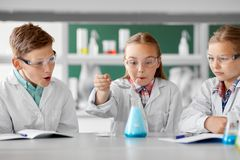 Kinder mit Reagenzglas Chemie in der Schule studierend lizenzfreie stockfotos