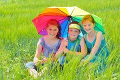 Kinder mit Regenschirm auf Feld Stockfotos