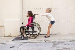 Kinder mit Rollstuhl Lizenzfreie Stockfotos