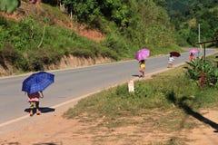 Kinder mit schützenden Regenschirmen der Sonne gehend hinunter die Straße lizenzfreies stockfoto
