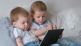 Kinder mit Tablette Zwei Jungenzwillingskleinkinder, die Karikatur der Tablette liegt auf dem Bett betrachten stock video footage