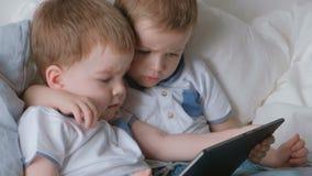 Kinder mit Tablette Zwei Jungenzwillingskleinkinder, die Karikatur der Tablette liegt auf dem Bett betrachten stock video